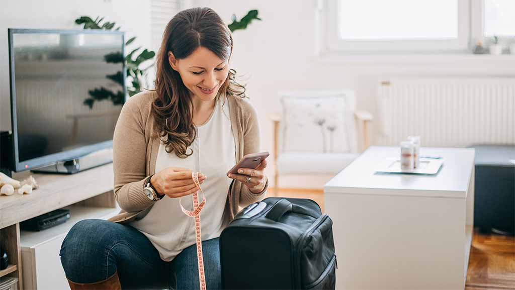 women measuring her baggage with her phone and a tape measure